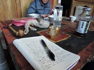 My notebook next to breakfast bowls of Baijo, the Dongba shaman's pipe, and Frog's wire artworks-in-progress, up on the mountains.